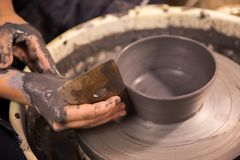 Womens hands at work on a potters wheel with black clay royalty free stock photo
