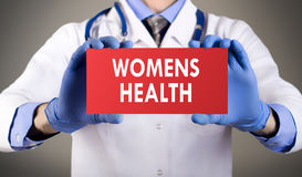 Womens health. Doctor`s hands in blue gloves shows the word womens health. Medical concept Stock Image