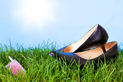 Womens high heel shoes and mobile phone on grass. Photo of womens high heel shoes and a mobile phone on grass against a bright blue sky with sunshine royalty free stock photo