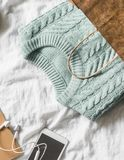 Womens knitted blue sweater in a paper bag and a smartphone with headphones on a light background, top view. Women`s clothing Royalty Free Stock Photography