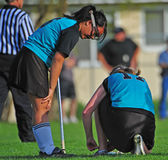Womens Lacrosse teammates. High School Girls lacrosse player talking to a team mate while she ties her shoe Stock Photography
