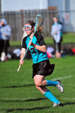 Womens LAX running. High School Girls lacrosse player running down the field Stock Image