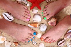 Womens legs in the sand and shells Royalty Free Stock Photography