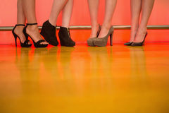 Womens legs wearing high heels. At a bar of nightclub Royalty Free Stock Photos