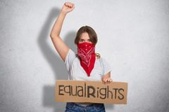 Womens Protest Concept. Serious Young European Female With Bandana On Face, Holds Plate With Inscription, Raises Hand Clenched In Royalty Free Stock Image