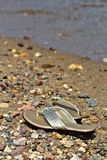 Womens Shiny Gold Sandals on Beach Royalty Free Stock Photography
