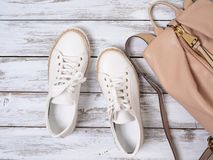 Womens shoes, accessories white leather sneakers, beige backpack. Fashion outfit, spring summer collection. Shopping concept. Flat lay, view from above royalty free stock photos