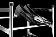 Womens shoes on a shoe rack. Womens shiny black shoes are laid on the chrome shoe rack royalty free stock photo