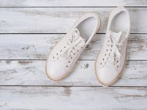 Womens shoes white sneakers on  wooden background. Spring summer collection. Fashion concept. Flat lay. Womens shoes white sneakers on wooden background. Spring stock images