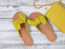 Womens shoes yellow leather sandals with knotted bow. Fashion outfit, spring summer collection. Shopping concept. Flat lay, view. From above royalty free stock images