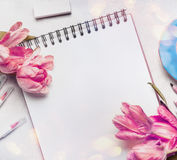 Womens springtime workspace with pale pink tulips, notebook or sketchbook and colorful brush markers royalty free stock photo