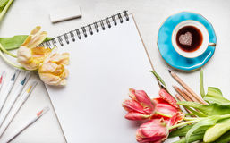 Womens springtime workspace with  pretty tulips, notebook or sketchbook , colorful brush markers and coffee cup Royalty Free Stock Photos