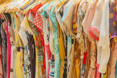 Womens summer clothes hanging on rail Stock Photos