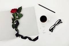 Womens working space with cup of coffee, pencil, empty notebook, glasses, black ribbon and rose flower on white table top view. Royalty Free Stock Photos