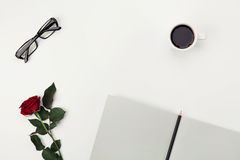 Womens working space with cup of coffee, pencil, empty notebook, glasses and rose flower on white table from above. Flat lay. Royalty Free Stock Photo