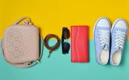 Womenshoes et accessoires de mode sur un fond en pastel jaune bleu Espadrilles, un sac, une bourse, une ceinture, lunettes de sol Photos stock