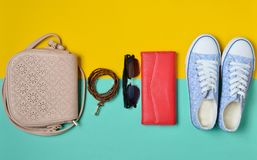 Womenshoes and fashion accessories on a blue yellow pastel background. Sneakers, a bag, a purse, a belt, sunglasses. Spring su. Women& x27;s shoes and fashion Stock Photos