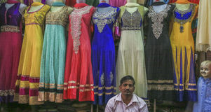 Womenswear Vendor, India. A salesman sits in front of colourful, sequinned women's dresses Royalty Free Stock Image