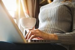 Womman unter Verwendung des Laptops und des Schreibens und des Haltens der Kaffeetasse stockfotos