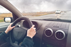 Woman Driving A Car. Hands of a female driver on steering wheel of a car on a cloudy winter day Royalty Free Stock Images