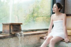 Womn enjoy the hot spring look outside. Beautiful young asian womn enjoy the hot spring look outside and sitting on poolside Royalty Free Stock Photography