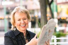 Womn feliz que reacciona al artículo periodístico imagenes de archivo