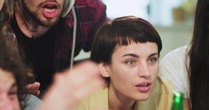 Womna do attractiv do close up com o cabelo curto que hildding uma garrafa verde com cerveja e que olha um fósforo de futebol apo video estoque