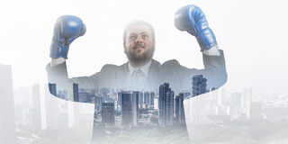 He won this battle. Businessman wear boxing gloves against modern cityscape Stock Image