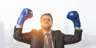 He won this battle. Businessman wear boxing gloves against modern cityscape Royalty Free Stock Photography