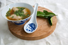 Won Ton Soup. A bowl of won ton soup garnished with coriander on a bamboo board with a spoon & kaffir lime leaves Royalty Free Stock Photos
