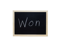 Won written with white chalk on blackboard Royalty Free Stock Photo
