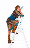 Wonan with paint brush. Young woman on step-ladder with paint brush photo Royalty Free Stock Photo