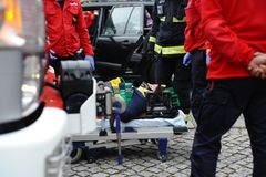 Wonded accident person on a litter. A injured person on a litter with security equipement and firefighters around Stock Image