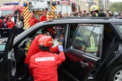 Wonded accident person removed from car. A injured person in the interior of crash car with security equipement and firefighters around.nDemonstration of Royalty Free Stock Photography