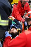 Wonded accident person straped on car interior. A injured person removed from interior of crash car with security equipement and firefighters straped her with Royalty Free Stock Photo