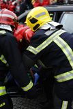 Wonded accident person straped on litter. A injured person removed from interior of crash car with security equipement and firefighters straped her with care Stock Photo
