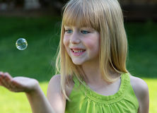 Wonder. Young girl catching an floating bubble Stock Photos