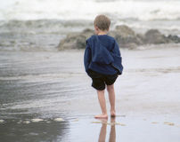 Wonder Of It All. Small boy holding up pant legs while wading in surf at the ocean royalty free stock image