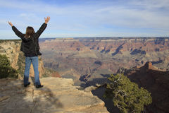 Wonder and Freedom at Grand Canyon. A woman raises her arms in wonder and amazement at the freedom represented by the grand canyon Royalty Free Stock Image