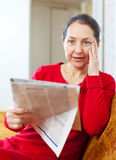 Wonder grief woman with newspaper. On sofa at home stock images