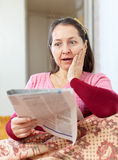 Wonder  mature woman with newspaper Royalty Free Stock Image