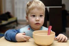 Wonder struck boy by the empty brown saucer with pink spoon. Wondering blond boy by the empty brown saucer with pink spoon Royalty Free Stock Image