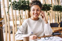 Wonder what your customer really wants? Ask. Don't tell. Attractive business woman working at desk in modern office. Portrait of happy young woman royalty free stock images