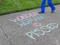 `Wonder Woman is Pissed` chalk on sidewalk. Corvallis, Oregon, August 14, 2017: `Wonder Woman is Pissed` chalk sign on sidewalk, with blue-clad legs passing by stock photo