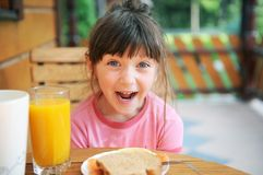 Wondered child girl has a breakfast outdoors Royalty Free Stock Images