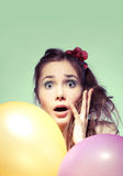 Wondered girl with balloons. Beautiful surprised girl with colorful balloons, green background Stock Photo