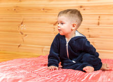 Wondered handsome boy looks at flying soap bubble indoors. On wooden  background Royalty Free Stock Photography