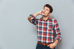 Wondered happy young man with mouth opened looking up. Over gray background Royalty Free Stock Images