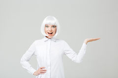 Wondered lovely woman with mouth opened holding copyspace on palm Royalty Free Stock Photos