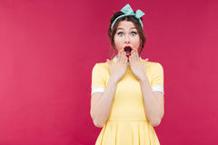 Wondered pinup girl in yellow dress with mouth opened Stock Photos